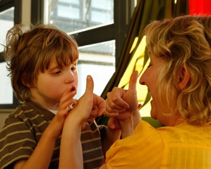 Child using tactile sign language.  Photo courtesy of www.sense.org.uk